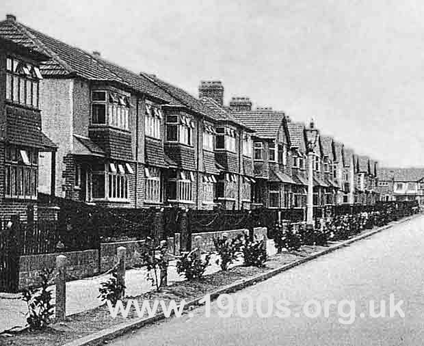 Row of 1930s-built semi-detached English suburban housing, photographed in the 1930s, showing iron railings and gas lamps (now gone)