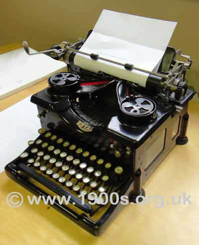 Vintage manual typewriter showing: the rollers holding the paper, the knob to wind the paper through the rollers, the lever to bring the rollers/paper back to position at the end of each line of typing, and the spools taking the two-colour typewriter ribbon