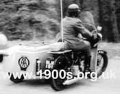 A man from the AA (Automobile Association) in the 1940s or 1950s, driving around by motor bike with sidecar to offer help to motoring AA members in difficulty.