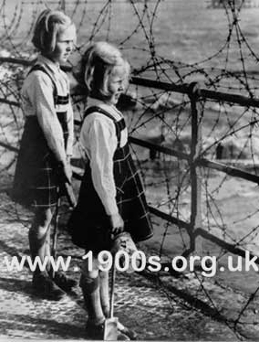 Barbed wire preventing wartime children playing on a beach