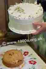 Decorated cardboard cake cover lifts to reveal a smallr cake in WW2