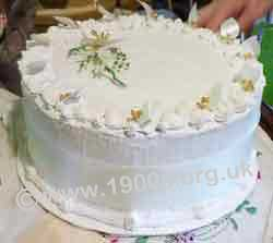Underside of ardboard cover decorated to look like a luxury wedding cake during