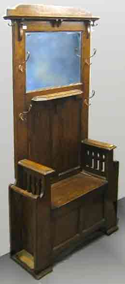Old hall stand for hanging coats and hats, a tall dark wooden piece of furniture with hooks, a mirror, seat with hinged lid over a container for gloves etc, and slots at the sides for umbrellas.