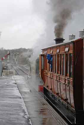 passenger leaning out of window of old steam train, train signal