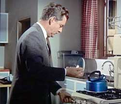 Lighting the gas under a blue anodised whistling kettle, 1950s or 1960s