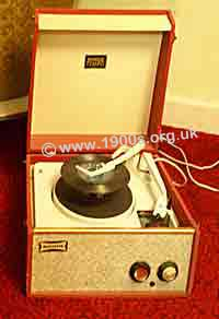 UK 1950s record play with an extended play record ready to drop onto the turntable; in practice there would have been several such records piled on top of one another.
