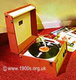 Record player from 1950s, UK, portable and housed in a box with a handle and latched lid.