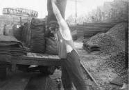 A coalman at a coal yard loading sacks of coal onto a delivery lorry, mid 20th century