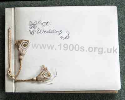 Wedding photo album, professionally produced, mid 20th century: bound in white leather cover embossed in silver with �Wedding�