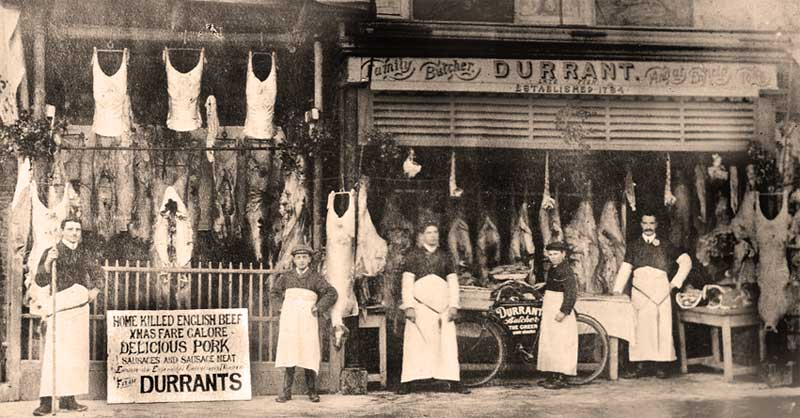 Butcher's shop in London in 1910, showing pork and beef hanging in the shop window and open to the street. Standing outside are the butcher, his assistants and a very young delivery boy with his bike.