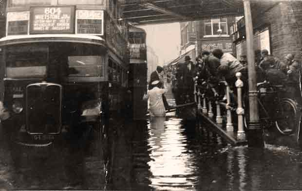 Flooding c1920: passengers getting on a bus via a plank, 2 of 2