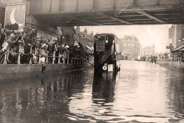 Flooding c1920: passengers getting on a bus via a plank, 1 of 2
