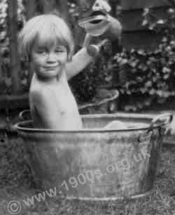 Child playing in a tin bath in 1930s London
