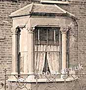 Typical bay window of the front parlour in an early 1900s house. Note the sash windows, the wooden venetian blinds and the lace curtains.