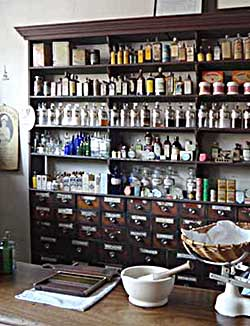 Bottles and storage drawers in a Victorian or Edwardian chemists' shop