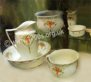 Decorative china wash set: matching wash bowl, hot water jug, slop bowl, soap dish, chamber pot and shaving jug as used in and before the early 1900s before there was running hot water.