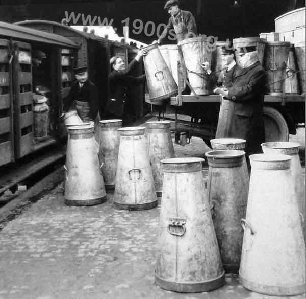 Loading milk churns onto a train, about 1920