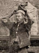 Coalman wearing traditional hat and coat carrying a sack of coal