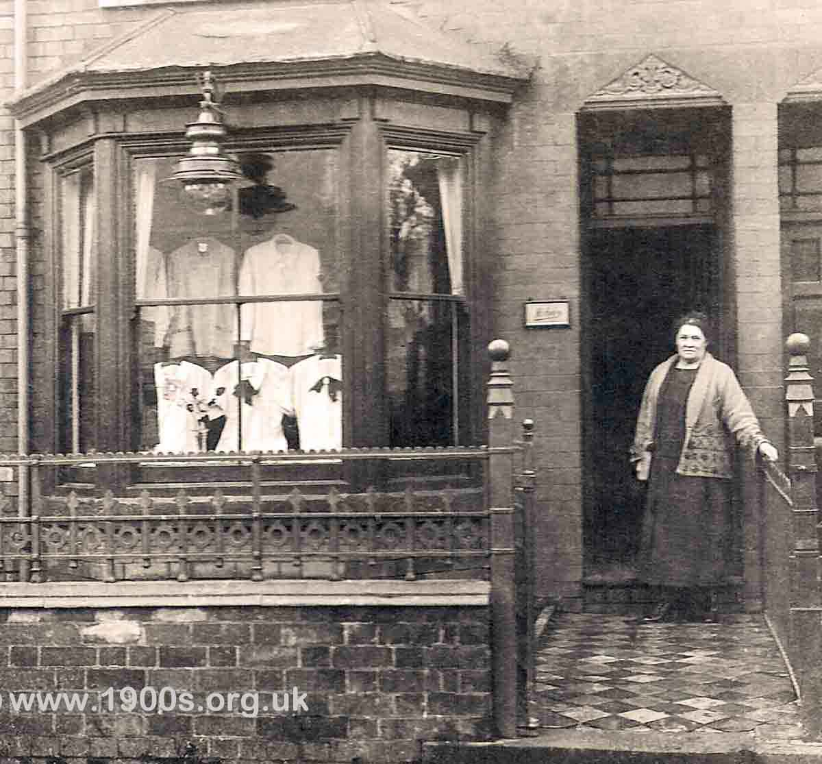 Outside of a 1925 fancy draper/haberdashery shop in the front room of a Victorian/Edwardian terraced house showing details of the tiled garden path, wrought iron railings, gas lamp, sash windows