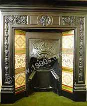 A typical black Edwardian fireplace with decorative tiles on either side