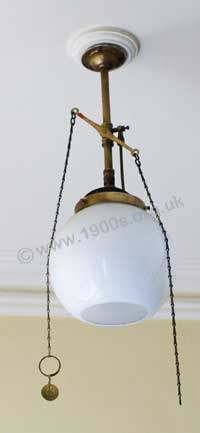 old gas ceiling lamp, showing its chains to control the flow of gas and hence the brightness of the glowing mantle.