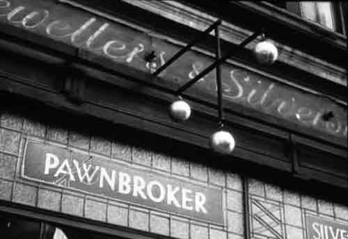 Old English pawnbroker's shop showing the name plate, glass front and pawnbroker sign of three gold balls