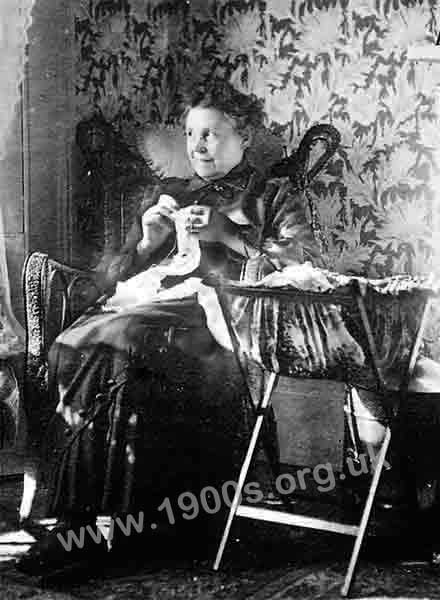 A working class woman sewing, mending and dressmaking in the early 1900s, showing her clothes, her needlework bag and her wickerwork chair.