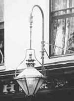 A typical privately-owned gas lamp suspended outside, over a shop window and contributing  		to the illumination of the streets in the early 1900s.
