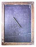 Lined side of a double-sided child's drawing slate from the early  		1900s; also a slate pencil