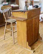 Teacher's high desk and high chair as used in schools in Victorian times, the early 1900s and into the 1940s or later.
