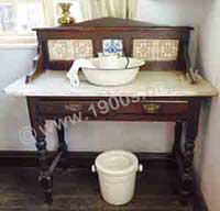 Old washstand, as used in Victorian and Edwardian Britain, with the customary marble top and the matching jug and bowl set. In this photo the jug and bowl set are made of enamel which would have been cheaper than decorated china.