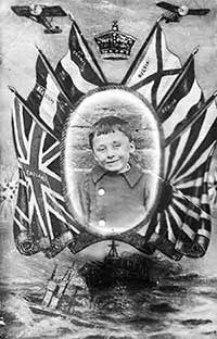 World War One propaganda photograph of a boy, showing him framed with the king's crown, the British flag, flags of the allies, fighter planes and a warship.